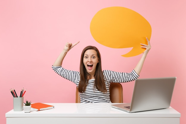 Excited girl holding yellow empty blank say cloud speech bubble work at white desk with pc laptop isolated on pastel pink background. achievement business career concept. copy space for advertisement.