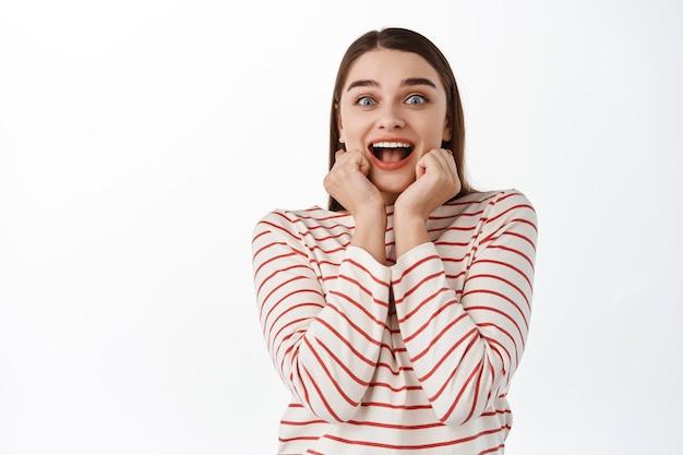 畏敬の念を抱く興奮した少女は、喜びと驚きから叫び、口の近くで手を握り、素晴らしいものを見つめ、スーパースターを見て驚いたように見え、白い壁の上に立っています