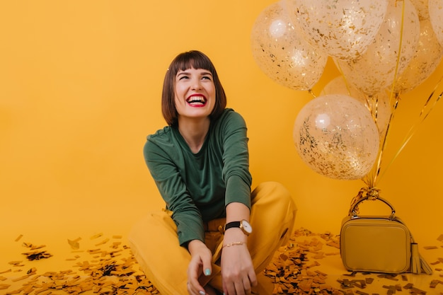 녹색 스웨터 파티 풍선과 함께 웃고 행복에 흥분된 소녀. 진정한 긍정적 인 감정을 표현하는 세련된 백인 여자의 실내 샷.