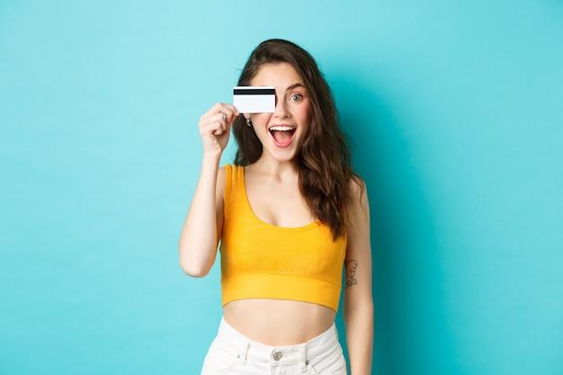 여름에 잘린 상의를 입은 흥분한 소녀는 카메라를 보고 놀란 표정을 짓고 신용카드로 쇼핑하고 파란색 배경 위에 서 있습니다.