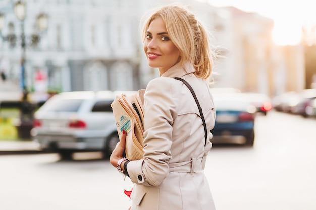 트렌디 한 코트를 입은 흥분한 소녀가 신선한 신문을 사서 집에 간다