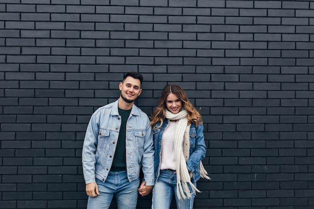 彼氏と手をつないでトレンディなデニムの衣装で興奮した女の子。レンガの壁に一緒に立っている愛情のあるカップルの笑顔。