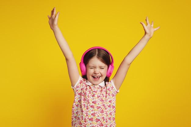 Взволнованная девушка в беспроводных наушниках кричит с закрытыми глазами и держит руки