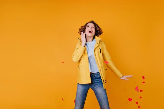Ragazza emozionante in jeans e cappotto di autunno che salta e che getta fuori i cuori di carta. romantica donna attiva che celebra il giorno di san valentino in studio.