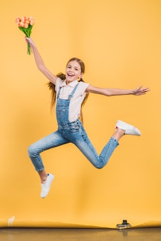 Excited girl jumping in air holding tulip bouquet in hand against yellow background