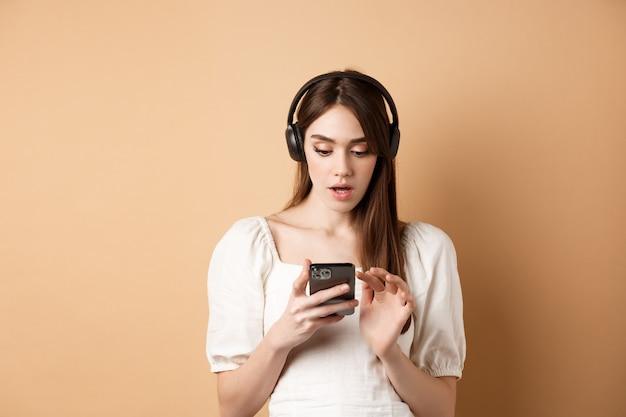 Возбужденная девушка слушает музыку в наушниках и изумленно глядя на смартфон, читая классные новости, нашла классный плейлист, стоя на бежевом.