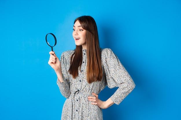 虫眼鏡を持って左を向いている興奮した女の子は、青の上に立って、調査または検索している興味深いプロモーションを見つけました。