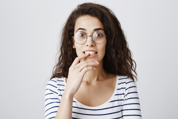 誘惑で探している興奮した女の子、興味をそそられる指を噛む