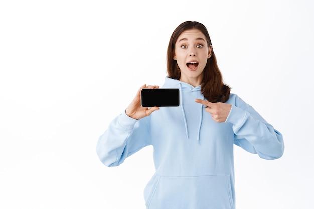興奮した女の子がスマートフォンの画面を水平に反転させて指さし、白い壁に立ってアプリケーションをデモンストレーションします