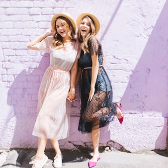 Excited girl in purple shoes standing on one leg beside friend in romantic long dress