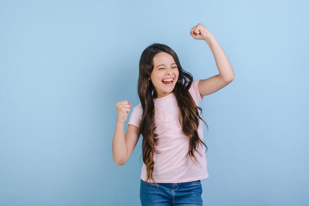Excited girl raised hands in success gesture in studio.