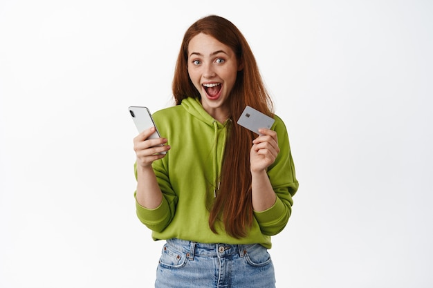 Excited girl shopping with smartphone app and credit card, scream happy from awesome discounts in online store, buying on sale, standing on white.