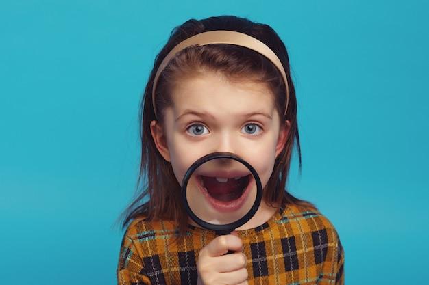 Возбужденная девушка показывает зубы через увеличительное стекло, изолированное на синем