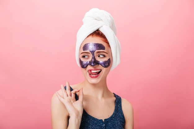 Excited girl showing okay sign during spa treatment. studio shot of happy young woman with towel and face mask isolated on pink background.