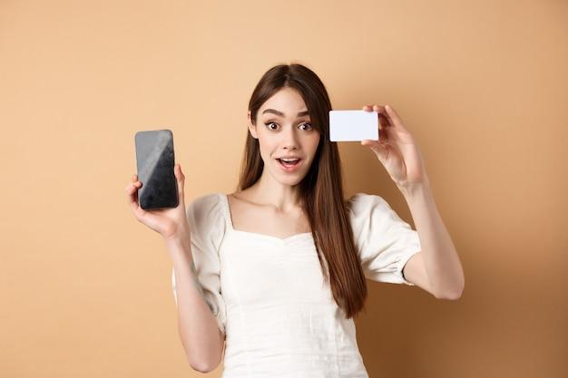 銀行のプラスチッククレジットカードと空の携帯電話の画面を表示し、ベージュの上に立って、ショッピングアプリを示す興奮した女の子。