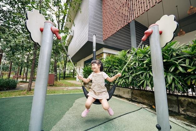 Возбужденная девушка качается на детской площадке