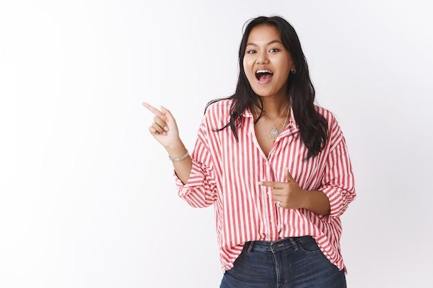 흥분된 소녀는 열정과 기쁨으로 웃고, 흰 벽 너머로 쇼핑하는 최고의 장소를 알고 있는 그녀의 초대로 왼쪽을 가리키며 재미있고 즐거운 판매에 대해 이야기합니다.