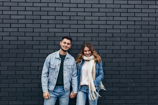 Excited girl in trendy denim outfit holding hands with boyfriend. smiling loving couple standing together on bricked wall.