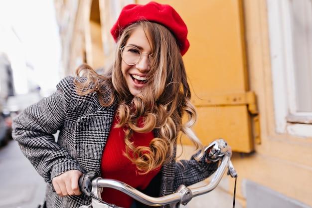 Ragazza emozionante con l'acconciatura riccia che guida sulla bicicletta nel fine settimana