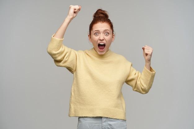 생강 머리를 가진 흥분된 소녀가 롤빵에 모였습니다. 파스텔 옐로우 스웨터와 청바지를 입고. 주먹을 움켜 쥐고 들어 올립니다. 소리를 지르고 승리를 축하하십시오. 회색 벽 위에 절연