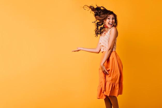 Возбужденная девушка с рыжими волнистыми волосами прыгает на желтом. студийный портрет блаженной молодой женщины в оранжевой одежде, танцующей с улыбкой.