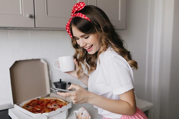 아침에 커피를 마시는 머리에 리본으로 흥분된 소녀. 아침 식사 중에 피자를 먹는 멋진 아가씨의 실내 샷.