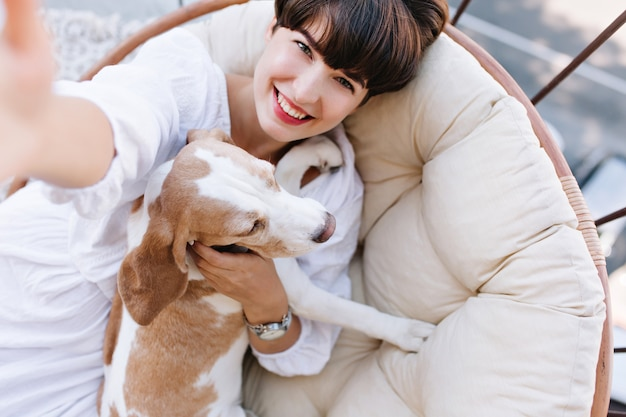 Excited girl with short brown hair laughing while taking photo of herself with beagle dog.