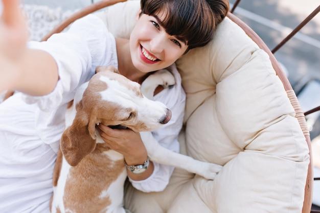 Ragazza emozionante con capelli castani corti che ride mentre prende la foto di se stessa con il cane beagle.