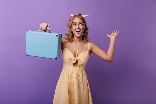 Ragazza emozionante con pelle abbronzata che tiene la sua valigia da viaggio. ridendo beata donna con la valigia che esprime emozioni positive.
