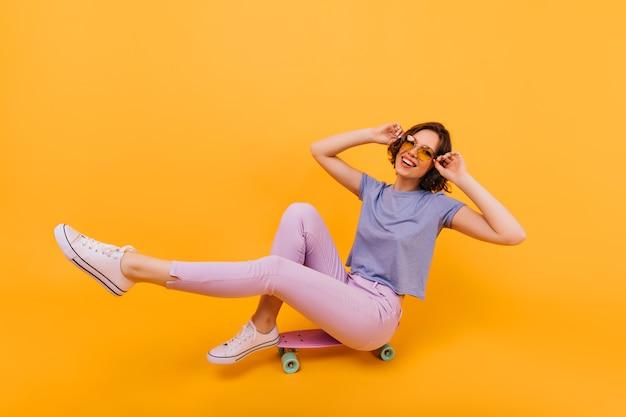 Ragazza emozionante in vetri di colore giallo che si siede sul longboard con un sorriso allegro. jocund signora europea con tatuaggio che esprime emozioni positive