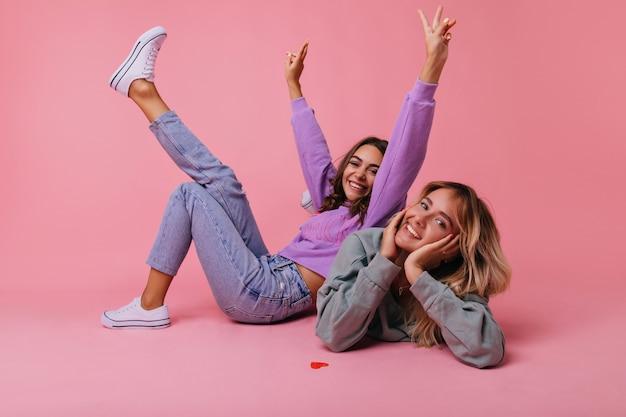Ragazze eccitate in abbigliamento casual primaverile in posa sul pavimento. migliori amiche positive che scherzano sul pastello.