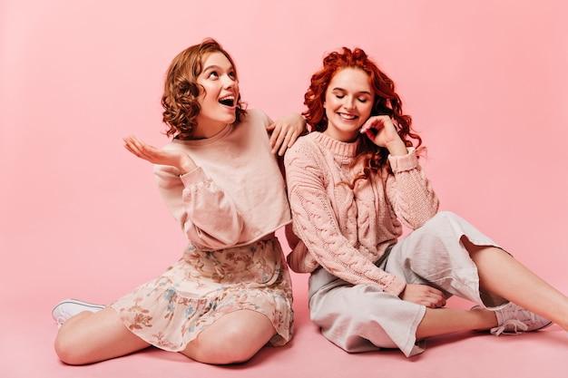 분홍색 배경에 웃 고 흥분된 여자입니다. 행복을 표현하는 여자 친구의 스튜디오 샷입니다.