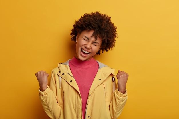 흥분된 기쁜 여자가 목표를 달성하고, 승리로 주먹을 쥐고, 대회 우승 후 진정한 챔피언이되고, 승리를 축하합니다.
