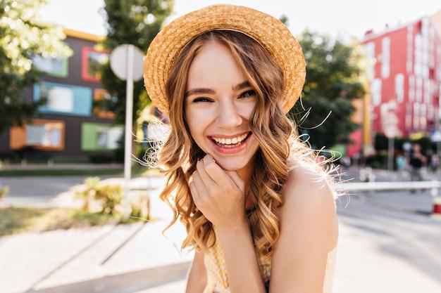 Donna felice eccitata che scherza durante il fine settimana estivo. modello femminile riccio accattivante in abito alla moda che gode del servizio fotografico.