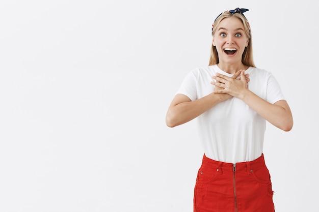 흰 벽에 포즈를 취하는 흥분된 기쁜 젊은 금발 소녀