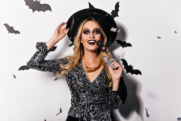 Возбужденная гламурная ведьма с черным макияжем смеется. улыбающийся белокурый вампир в шляпе, расслабляющейся в хэллоуин.