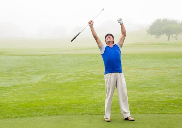 Excited golfer cheering on putting green
