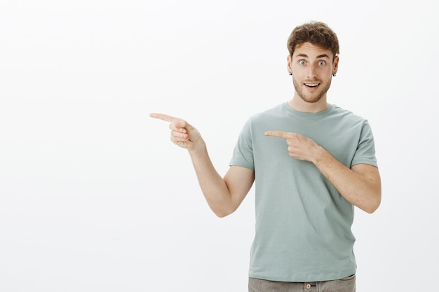 Взволнованный симпатичный парень в серьгах и футболке, указывая влево указательными пальцами и широко улыбаясь, спрашивает, не хотят ли друзья пойти с ним