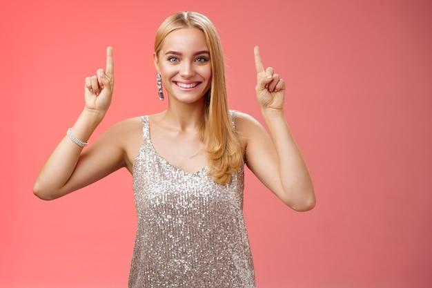 Возбужденная великолепная белокурая европейская женщина в серебряном блестящем элегантном платье поднимает руки вверх, показывая впечатляющую невероятную рекламу, улыбаясь, радостно взволнованная, хочу взглянуть поближе, красный фон.