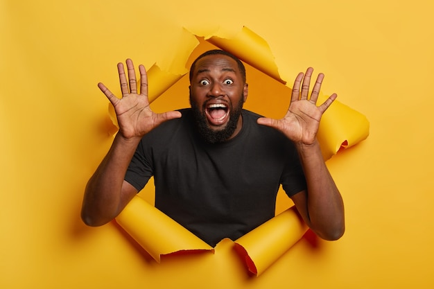 Excited greatly surprised dark skinned guy keeps mouth and eyes wide opened, raises palms, wears black t shirt, stands in torn yellow paper wall. emotions concept.