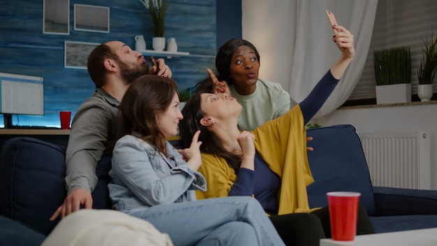 Excited group of multiracial friends sitting on sofa during joyful party taking selfie