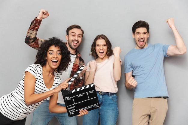 映画製作のカチンコを持っている友人の興奮したグループ。