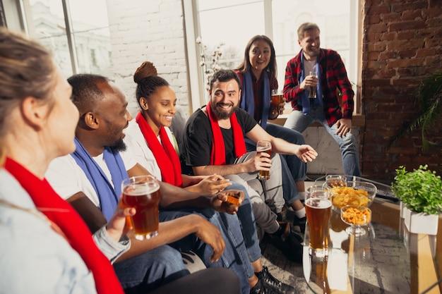 自宅でサッカースポーツの試合を見ている人々の興奮したグループ