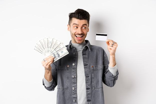 Excited guy holding plastic credit card and dollar bills, standing amused on white background.