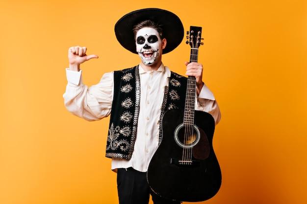 ギターを持っているメキシコの伝統的な服を着た興奮した男。ハロウィーンパーティーで楽しんでいる幸せな死んだ歌手。 無料写真