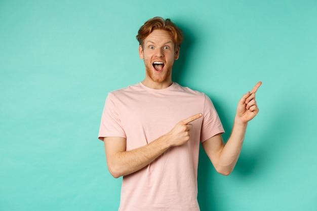 민트 배경에 광고를 표시하는 분홍색 티셔츠에 흥분된 남자, 카메라에 놀란 찾고 오른쪽 상단을 가리키는.