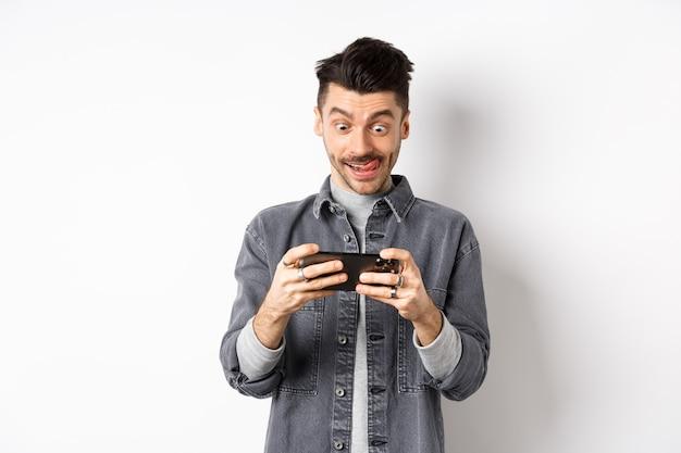 焦点を合わせた顔で携帯電話でビデオゲームをプレイしている興奮した男、スマートフォンの画面をタップし、携帯電話を水平に保持し、白い背景。