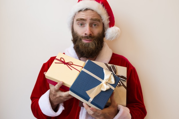 Excited guy wearing santa costume and holding gift boxes