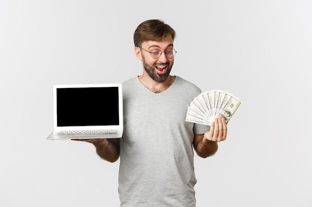 Взволнованный парень работает фрилансером, показывая ноутбук и деньги