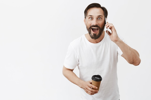 Excited handsome adult man drinking coffee and talking on smartphone